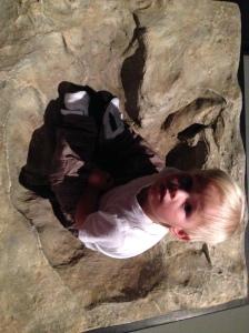 James inside a tyrannosaurus rex's footprint