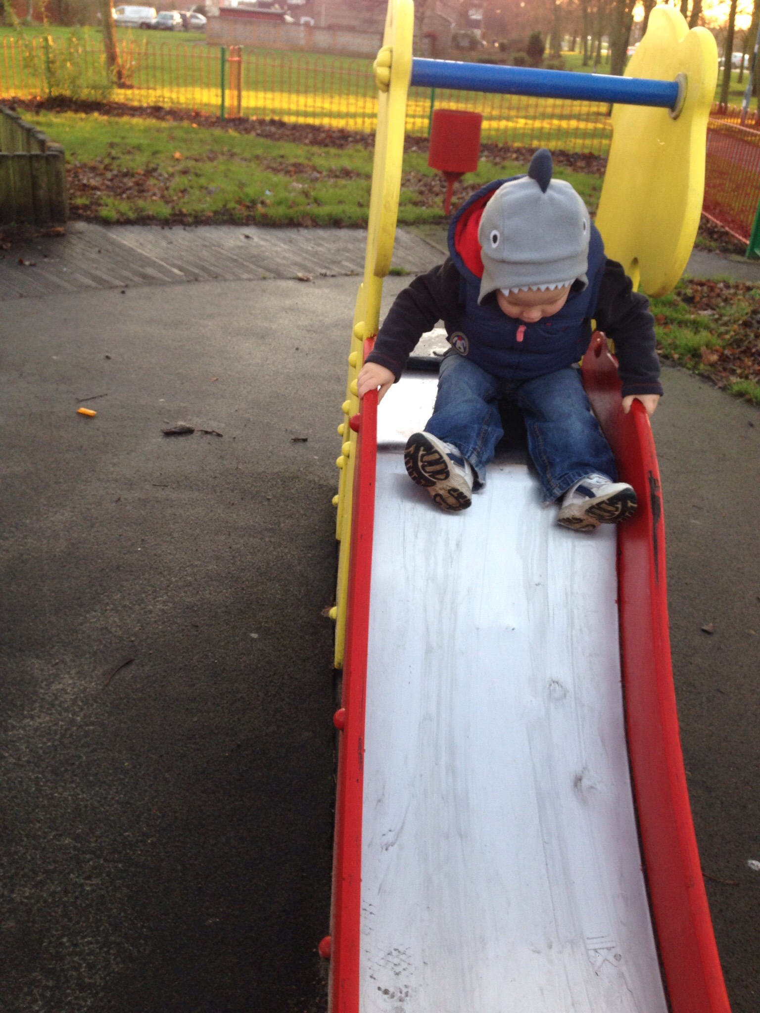 toddler getting ready to push himself down a slide