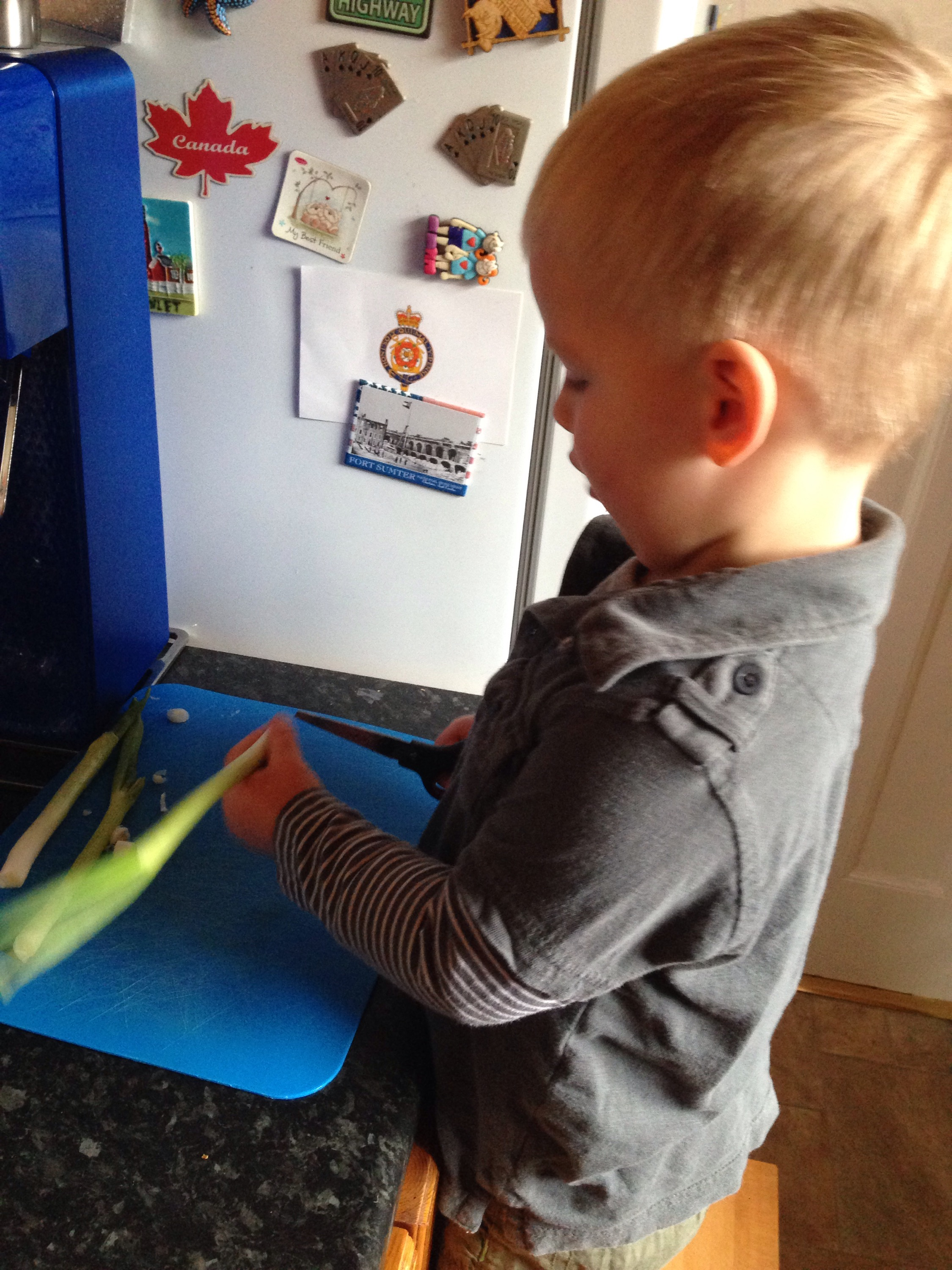 toddler cutting a spring onion to make pea fritter