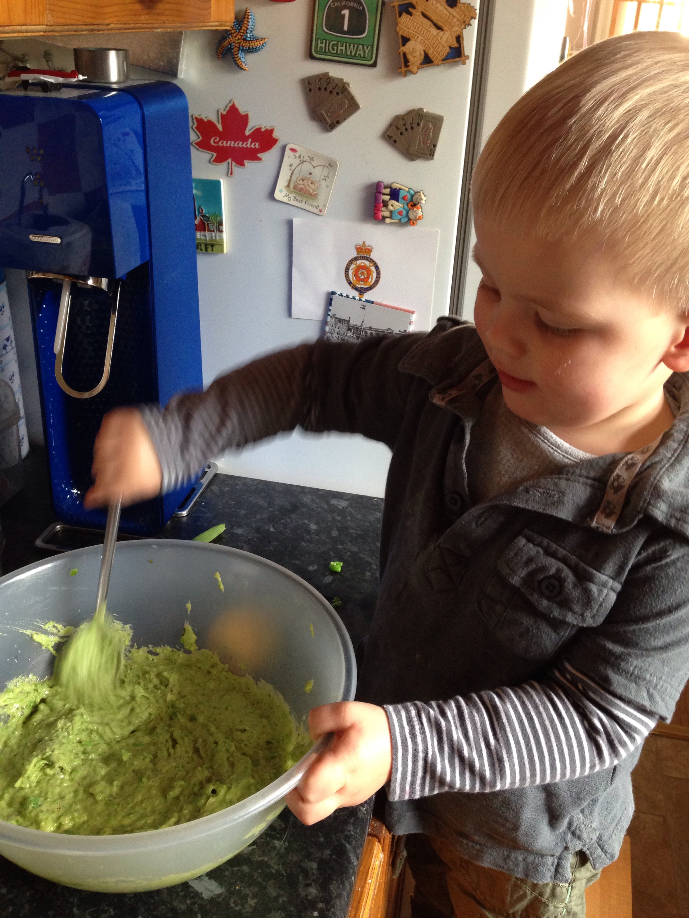toddler stirring the gloopy, green mixture making pea cakes