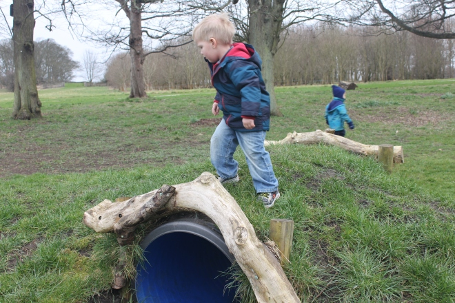 toddler on grass hill over tunnel at Seaton Delaval Hall