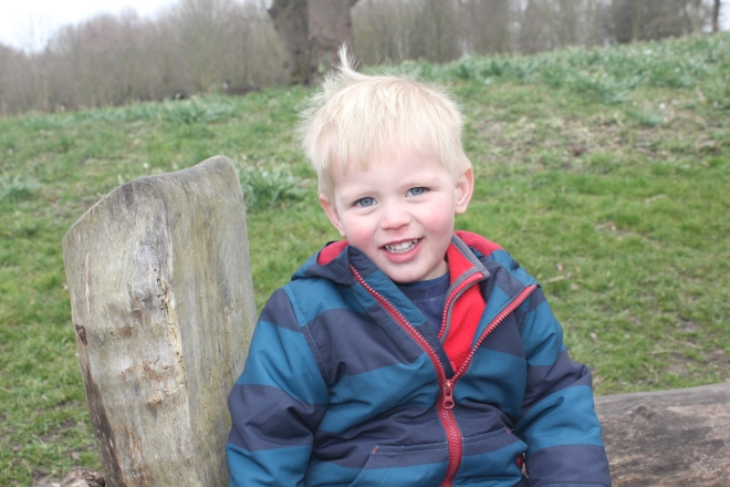 toddler smiling on log chair at seaton delaval hall
