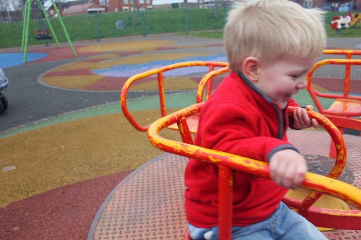 toddler smiling on roundabout pearson park playground north shields