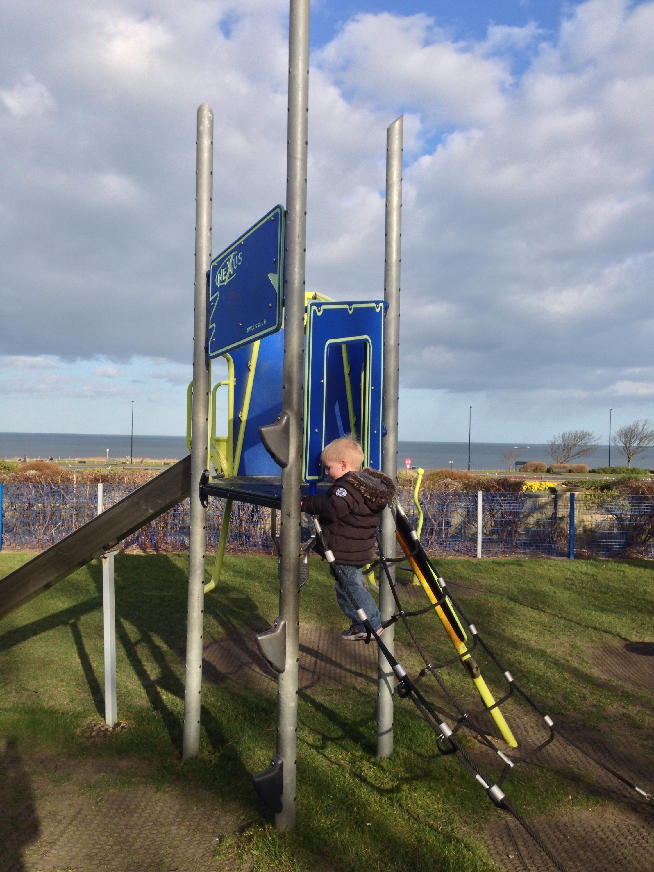 toddler on climbing frame with view of sea