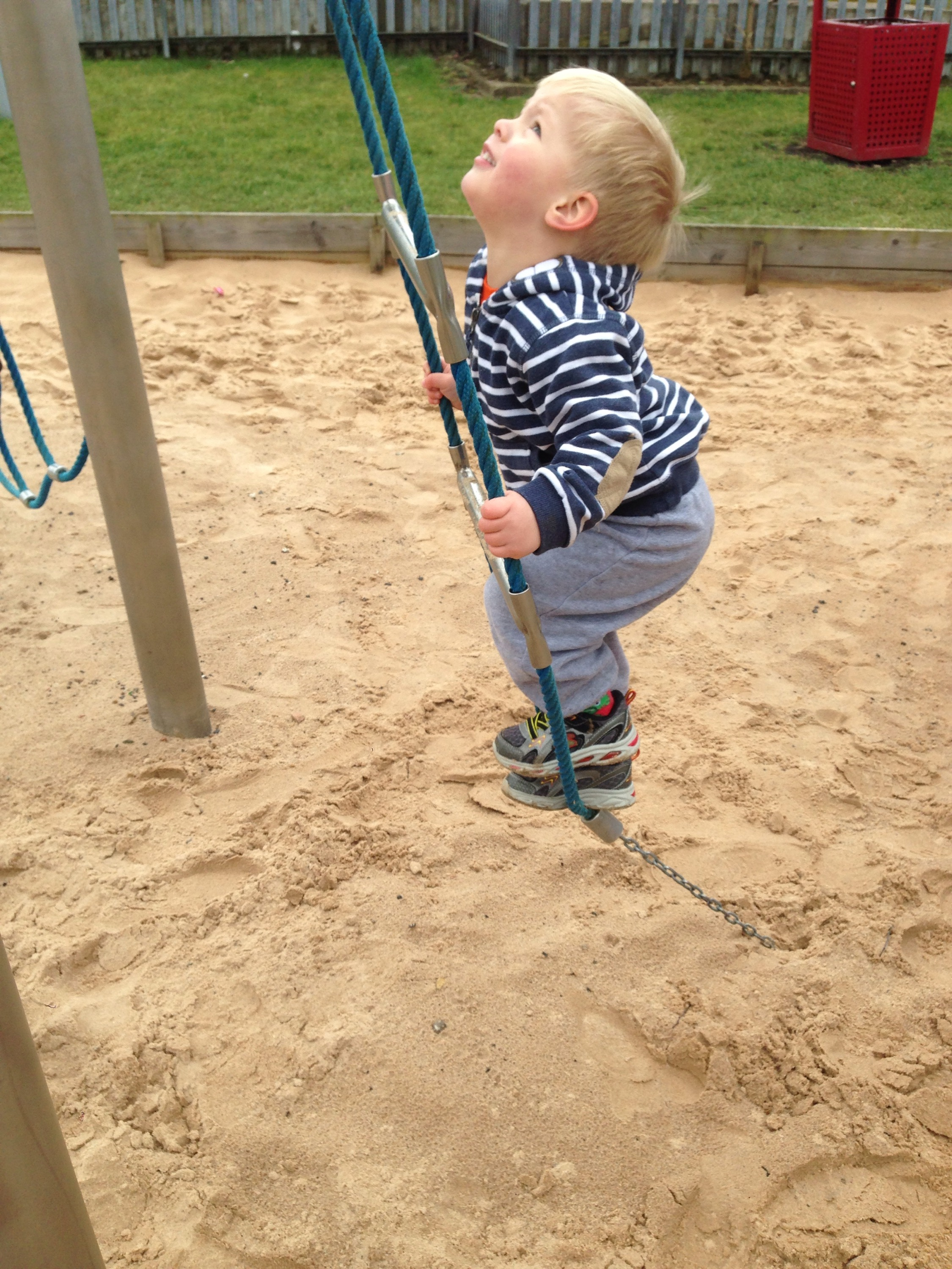 toddler on ladder with sand behind