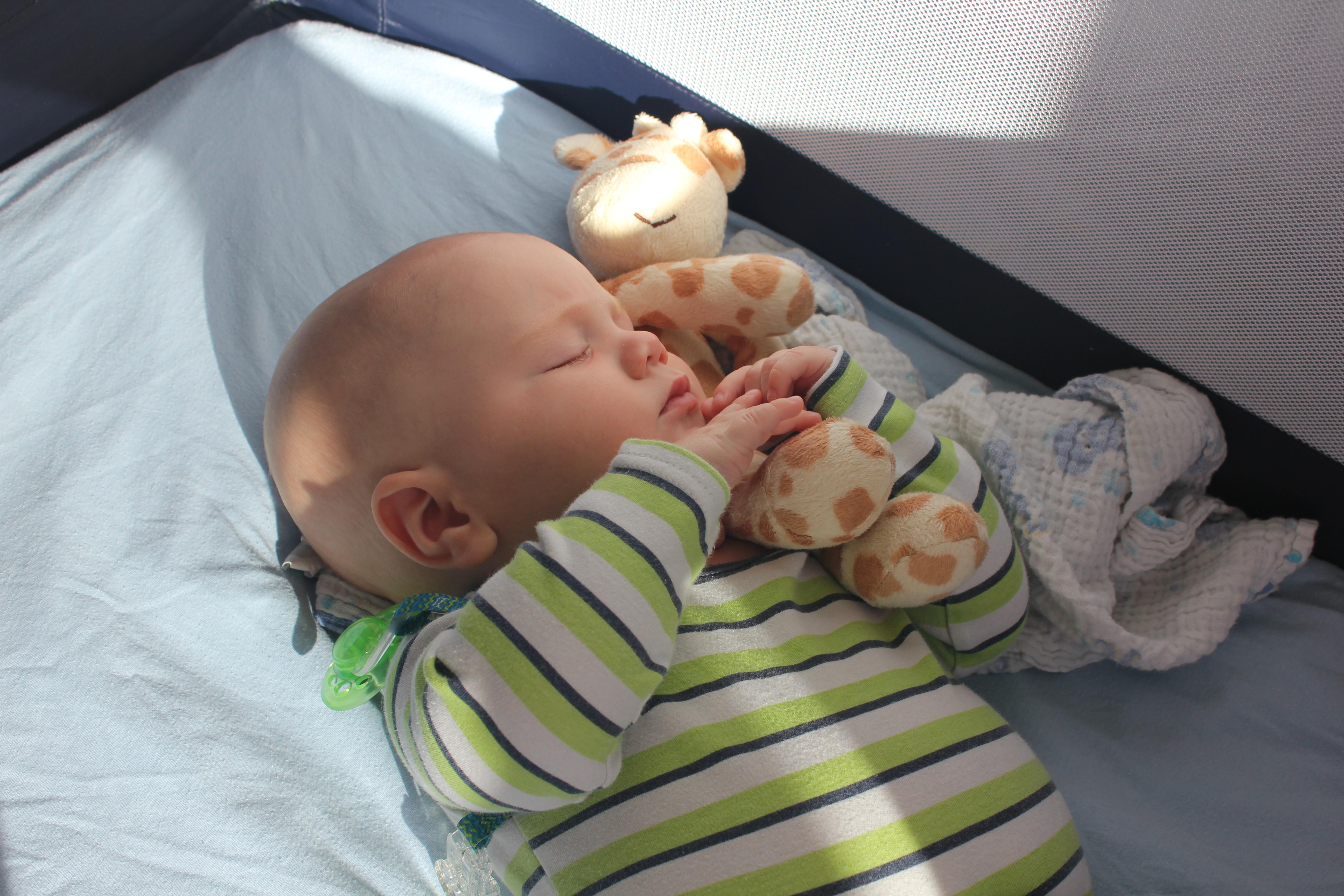 baby asleep travel crib giraffe